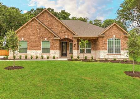 Fairview finished home street view with green front lawn, custom brick finished siding, and stone wall accent
