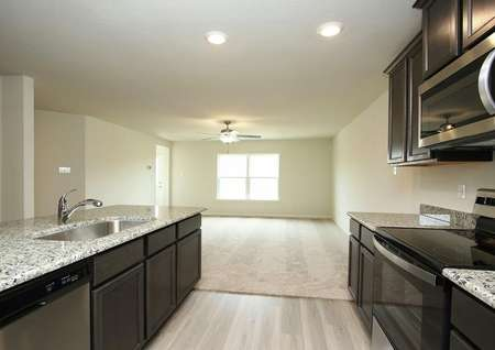 Photo of kitchen with dark brown cabinets, polished gray granite counters, plank flooring looking into carpeted living room with ceiling fan and double window to back yard.
