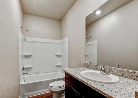 Jasper bathroom completed with granite countertop, white fixtures, and a bath/tub combo
