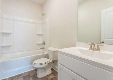 Alexander guest bath with white fixtures, large vanity, and shower/bathtub unit