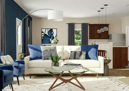 Rendering of living room focused on white   couch with blue and gray pillow, with dining and kitchen areas in the   background