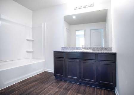 Pennington bathroom with wall-mounted light fixture, brown cabinet space, and hardwood floors