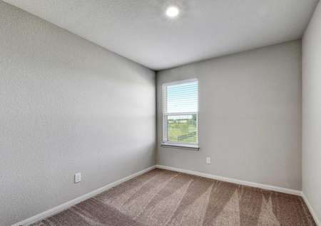 Carson bedroom with brown carpeting, white trimmed grey walls, and white framed window