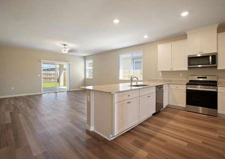 The kitchen has sprawling countertops, white cabinetry and stainless steel appliances.