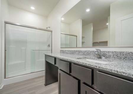 A bathroom in the Del Mar floor plan with a walk-in shower that has sliding glass doors and wood-like floors in the bathroom.