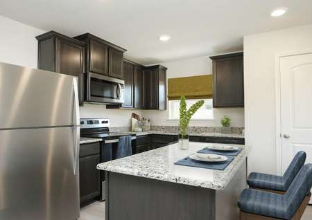 Staged kitchen with dark brown cabinets, stainless appliances, island with two barstools and window over the sink, pantry door visible.