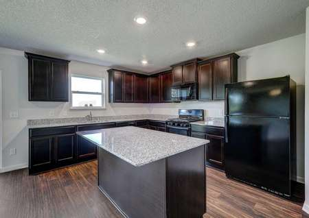 Pennington kitchen with brown cabinets, black refrigerator, and recessed lights
