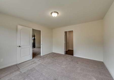 Blanco bedroom with overhead light fixture, brown carpet, and private bathroom
