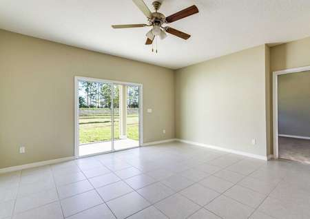Living room with tile flooring, a sliding glass door to the backyard, tan walls and white baseboards in the Wekiva floor plan.