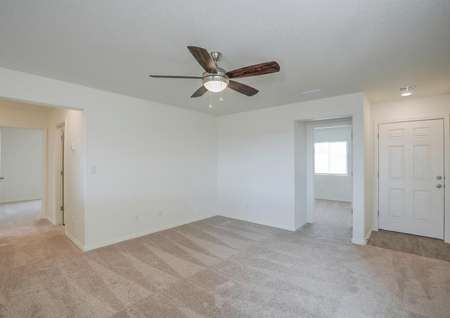 Family room with tan carpet and a ceiling fan.