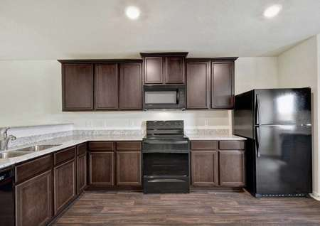 Hawthorn kitchen with wooden cabinets, recessed lights, and black appliances