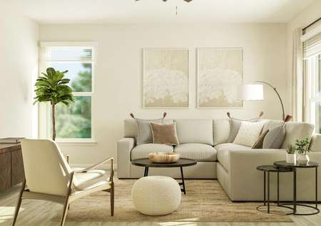 Rendering of the living room in the   Jordan floor plan. The space has two windows and wood-look flooring. It is   decorated with a gray sectional couch, an armchair, side tables and a coffee   table.