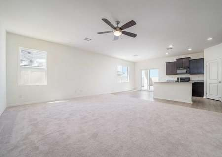 Balboa great room with carpeted floors in the family room, overhead fan and lights, and kitchen counter