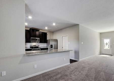 Carson great room with carpet flooring, recessed lights in the kitchen, and large granite countertop