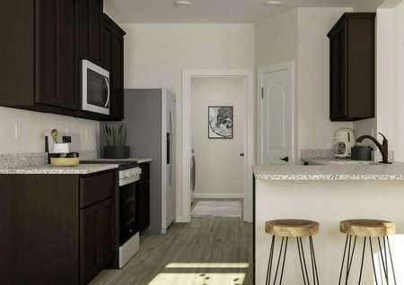 Rendering showing the kitchen with   granite counters, dark brown cabinetry and stainless steel appliances. Three   barstools are at the counter and the laundry room is visible through an open   doorway.