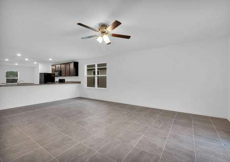 Spacious living room in the St. Martin floor plan that has a ceiling fan with a light fixtureand a window by the kitchen breakfast bar.