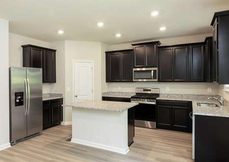 The Mid Atlantic Conway kitchen showing a granite island, stainless steel appliances and dark brown cabinets.