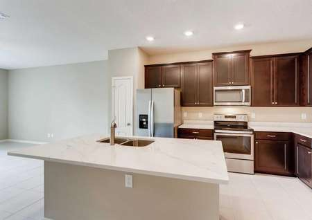 Kitchen in the Mateo model with large quartz kitchen island, dark brown upgraded cabinetry and stainless steel appliances