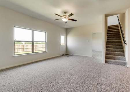 This home has a large family room with a ceiling fan and back yard views.