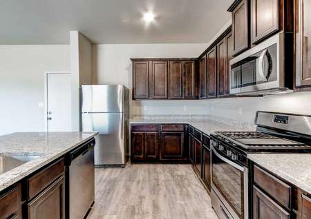 Snowflake kitchen with stainless steel applianecs, brown cabinetry and granite countetops