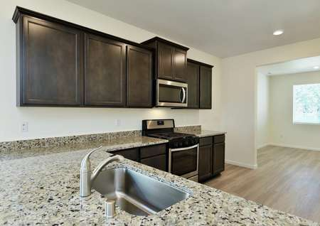 Kitchen with granite breakfast bar, single basin sink and dark brown cabinetry.