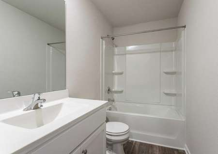 Hartford bathroom with white fixtures, brown tile flooring, and bathtub-shower combo unit