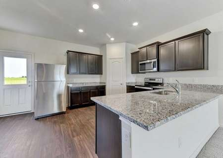Travis kitchen with wood flooring, brown cabinetry, and stainless steel appliances