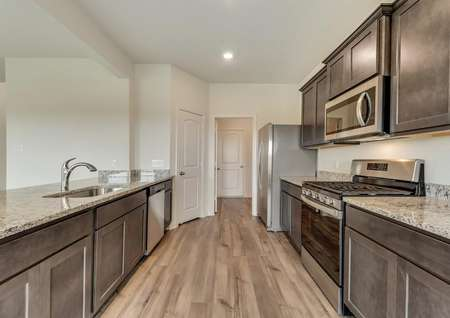 The kitchen has sprawling granite countertops, brown cabinetry and stainless steel appliances.