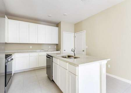 The Wekiva floor plans kitchen that has tan walls with white baseboards, quartz countertops and white cabinets.