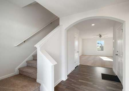 Avery interior hallway with carpeted stairs, white walls, and brown tile floors