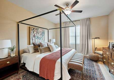 Bedroom with a canopy bed, wooden dresser and night stands on either side of the bed.
