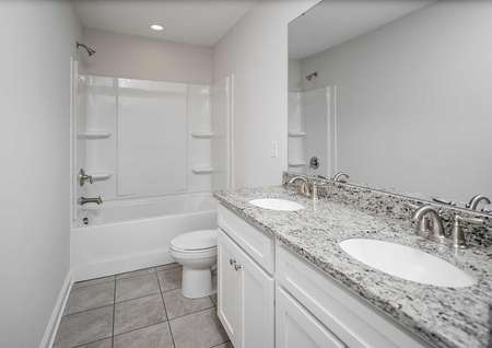 A tile-floored bathroom in the Kiawah floor plan with whitecabinets, two-sinks and granite countertops.