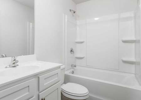 Avery guest bathroom with white fixtures, bath-shower combo, and large vanity