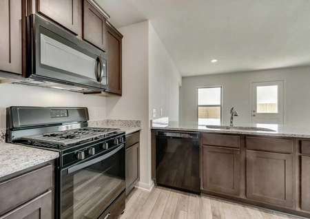 Rio Grande house kitchen with brown wood cabinetry, granite counters, and black appliances