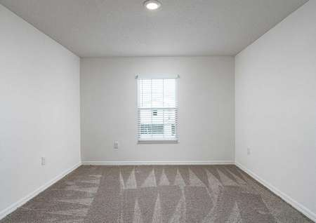 Carpeted spare bedroom with recessed lighting and a window that lets in natural light.