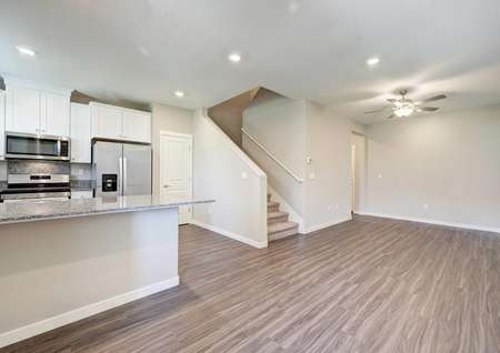 Wide view of the Kennedy floor plans living, dining and kitchen area with a staircase to go upstairs.