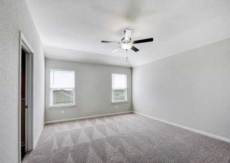 Shelby bedroom with white trimming on gray walls, light brown carpet, and overhead fan