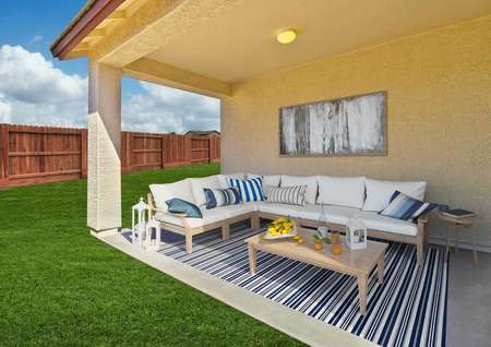Prescott porch staged with outdoor sectional sofa with white cushions, wicker coffee table, and a striped throw rug in grey and blue