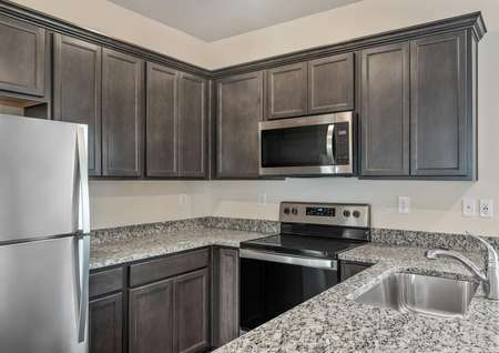 The kitchen has brown cabinetry and a full suite of stainless steel appliances.