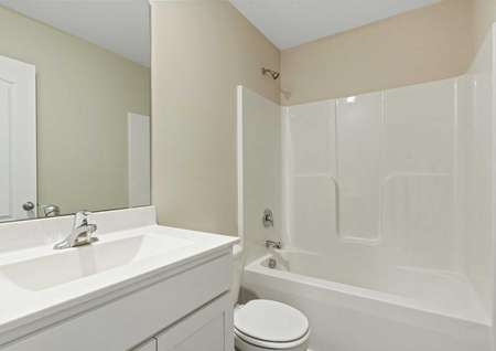 Alamance bathroom with modern fixtures - sink, toilet, and shower-tub combo