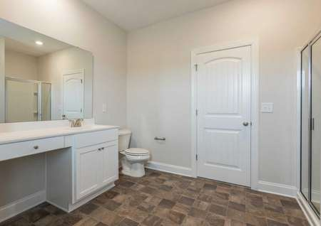 Burton master bathroom with large vanity, white appliances, and walk-in shower