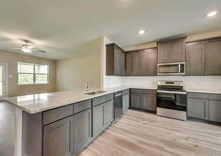 The spacious kitchen in the Texoma floor plan with wood-like floors, recessed lighting, granite countertops and brown cabinetry.
