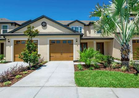 Exterior view of the Calabria floor plan model that has grass, bushes and a small palm tree in the front yard.