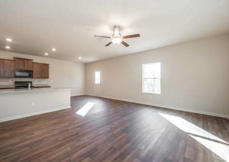 Burke great room with hardwood floors, off white wall paint, and white baseboards