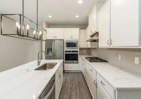 Show-stopping kitchen featuring beautiful quartz countertops, white cabinets and modern appliances.