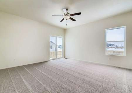 Interior photo of spacious family room with a window and sliding glass door, carpet and ceiling fan.