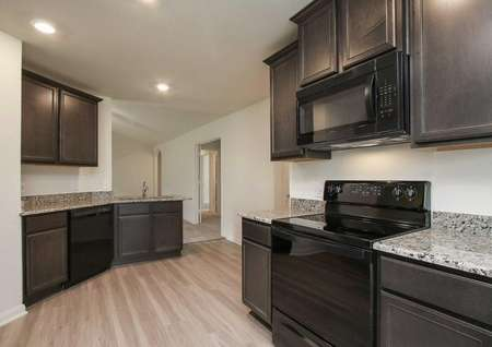 Pecos kitchen with recessed lights, black appliances, and brown custom cabinets