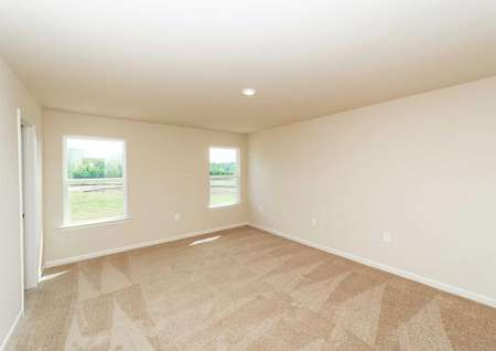Spacious carpeted master bedroom with two windows in the Hartwell floor plan