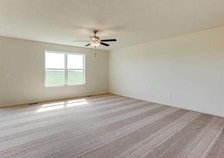 Nicollet family room with overhead ceiling fan, light brown carpet, and large backyard