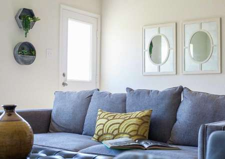 Model home staged with blue sofa with brown pattern throw pillow, mirror mounted on the wall, and decorative plants on the other wall